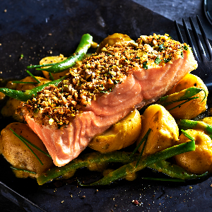 Pistachio Crusted Salmon Topped with Orange Pur Blanc served with Gratin Potatoes and Vegetables